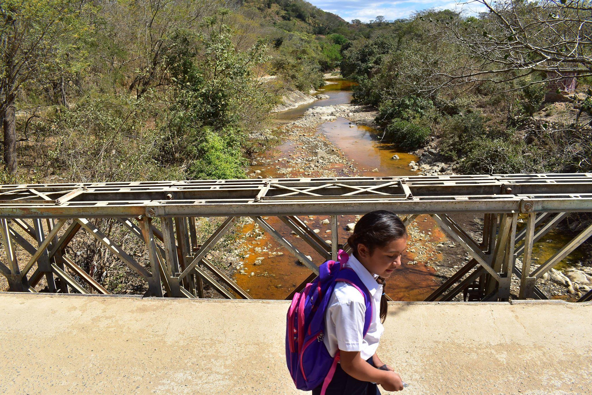 Niña regresa de escuela atravesando puente